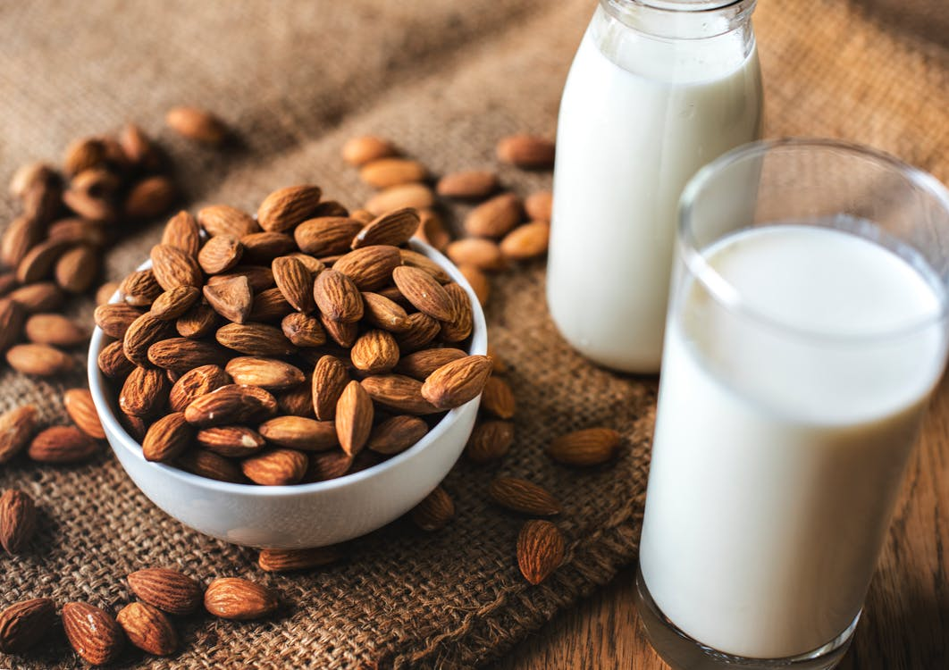 Clear Glass With Milk Beside the Bowl Full With Almonds