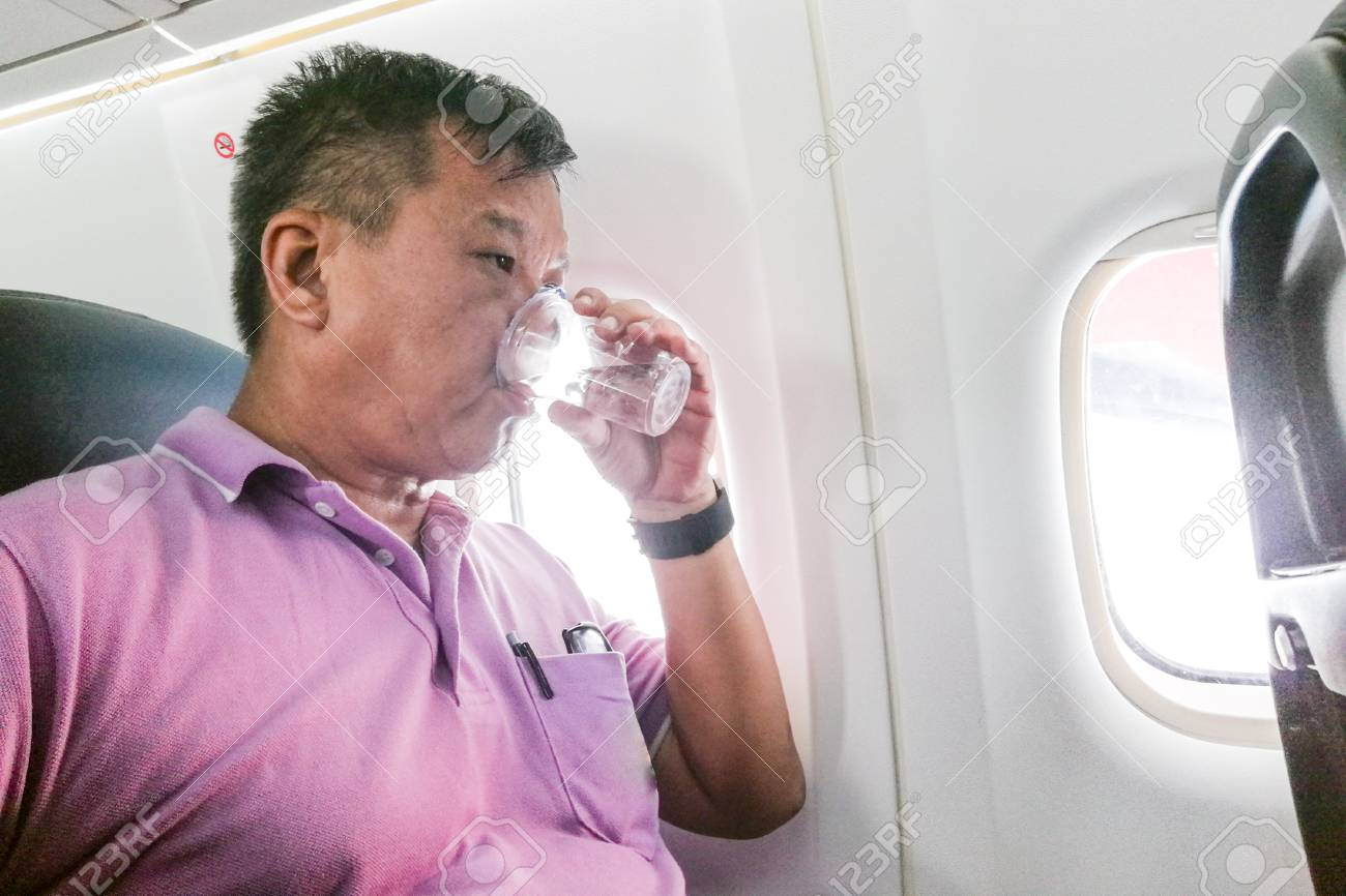 Person Drinking Water In Airplane Long Haul Flight To Hydrate.. Stock Photo, Picture And Royalty Free Image. Image 86873200.