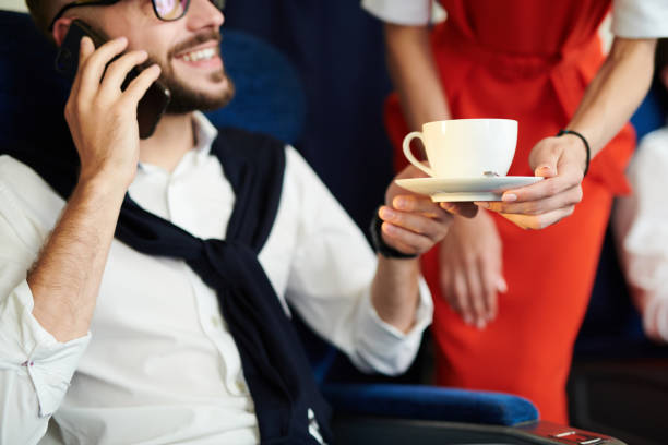 First Class Service in Plane Close up of unrecognizable flight attendant serving cup of coffee to handsome man sitting in first class and enjoying flight, copy space business class flight stock pictures, royalty-free photos & images