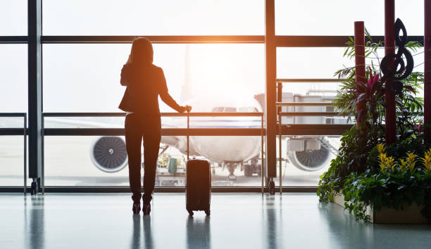 Silhouette of business traveler makes a call while waiting for her flight Silhouette of business traveler makes a call while waiting for her flight. business class flight stock pictures, royalty-free photos & images